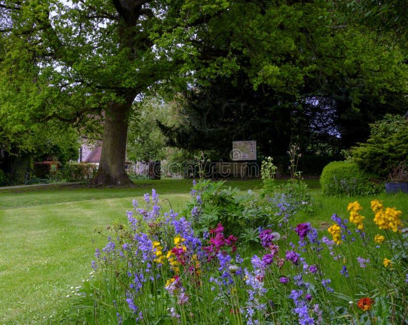 Sikt in mot Sts Mary kyrka ?ver de l?sa rabatterna och gr?smatta av det Pleistor huset i Selborne, Hampshire, UK royaltyfri bild