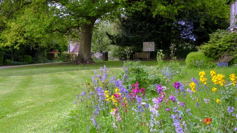 Sikt in mot Sts Mary kyrka ?ver de l?sa rabatterna och gr?smatta av det Pleistor huset i Selborne, Hampshire, UK royaltyfria foton