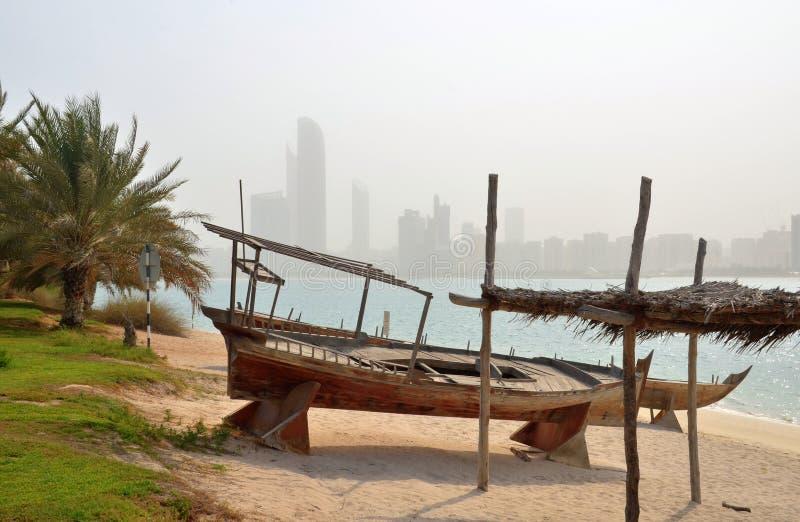 Sikt på Abu Dhabi horisont med det traditionella fartyget i förgrunden, UAE royaltyfri fotografi