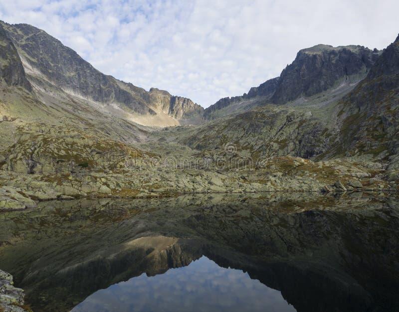 Sikt på den bergsjöProstredne Spisske plesoen höga Tatras i Slovakien med blå himmel för bergkantnd som in reflekterar royaltyfri bild