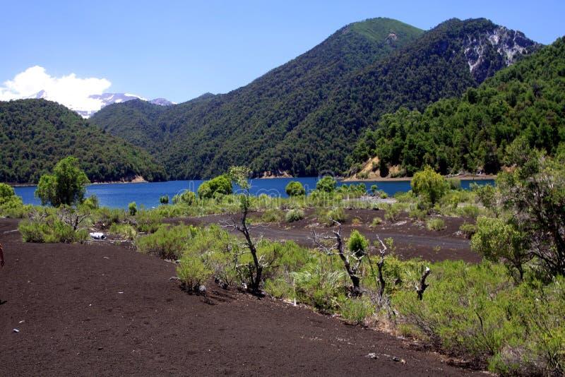 Sikt på den djupblå kratersjön som omges av berg med snö korkade Volcano Llaima på Conguillio NP i centrala Chile royaltyfri fotografi