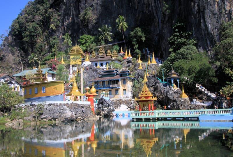 Sikt på den färgrika kitschy templet med guld- torn som reflekterar i en sjö mot brant den bergframsida och bron arkivfoton