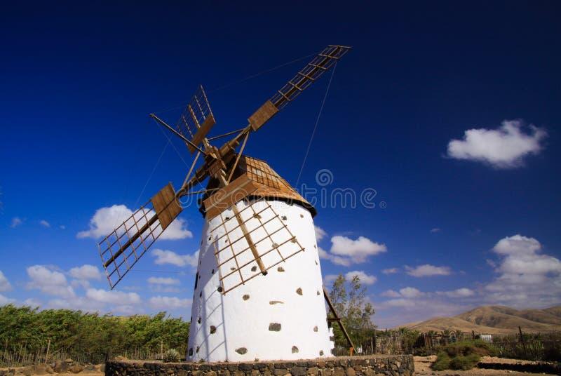 Sikt på den forntida vita väderkvarnen med bruna vingar mot blå himmel med få spridda moln - Fuerteventura, El Cotillo arkivfoto