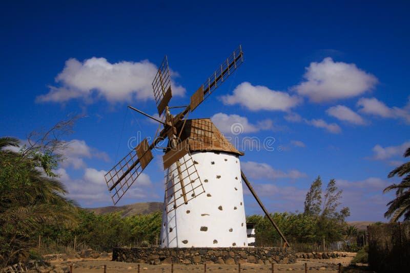 Sikt på den forntida vita väderkvarnen med bruna vingar mot blå himmel med få spridda moln - Fuerteventura, El Cotillo arkivfoton