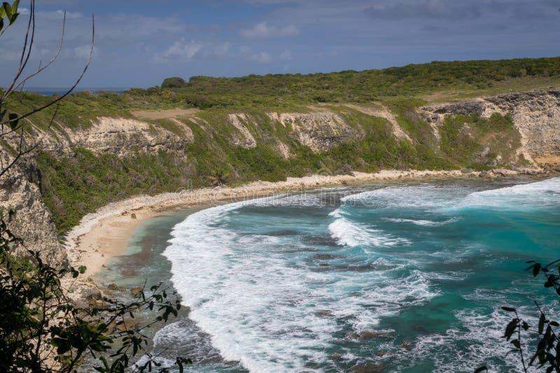 Sikt på den härliga fjärden med stora vågor i Guadeloupe - Plage de la Porte D ` Enfer du Moule Sätta på land på porten till helv fotografering för bildbyråer