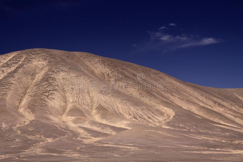 Sikt på den karga torra bruna isolerade kullen som kontrasterar med djupblå himmel i salar de atacama - Chile arkivfoto