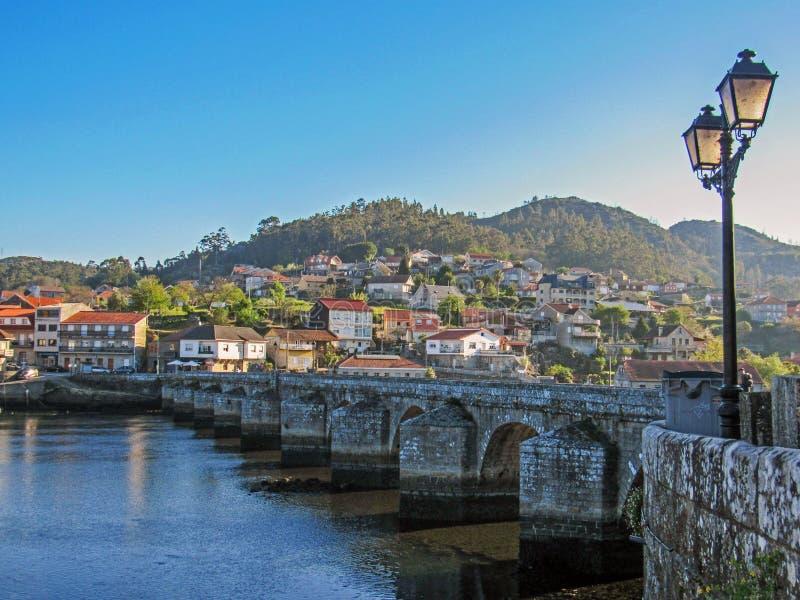 Sikt på den medeltida bron till och med floden och den lilla bergstaden med röda tailed tak, bygd Portugal arkivfoto