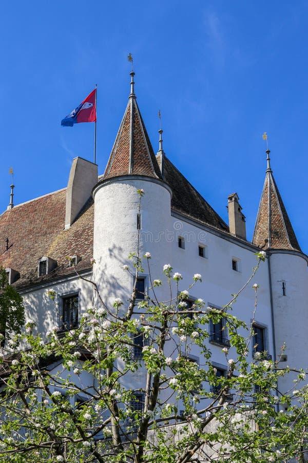 Sikt på den Nyon slotten med flaggan som vinkar på taket till och med blommande träd royaltyfri foto