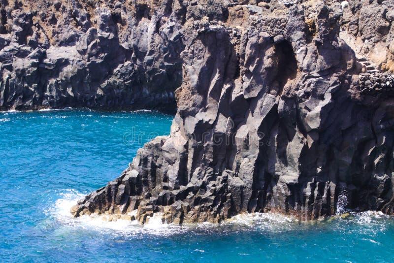 Sikt på den ojämna grova kustlinjen med skarpa klippor lagun med turkosblått vatten, vågor - Los Hervidereos, Lanzarote arkivbilder