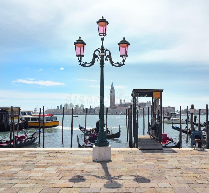 Sikt på den Venedig lagun med lyktan och gondoler och San Giorgio Maggiore på bakgrund fotografering för bildbyråer