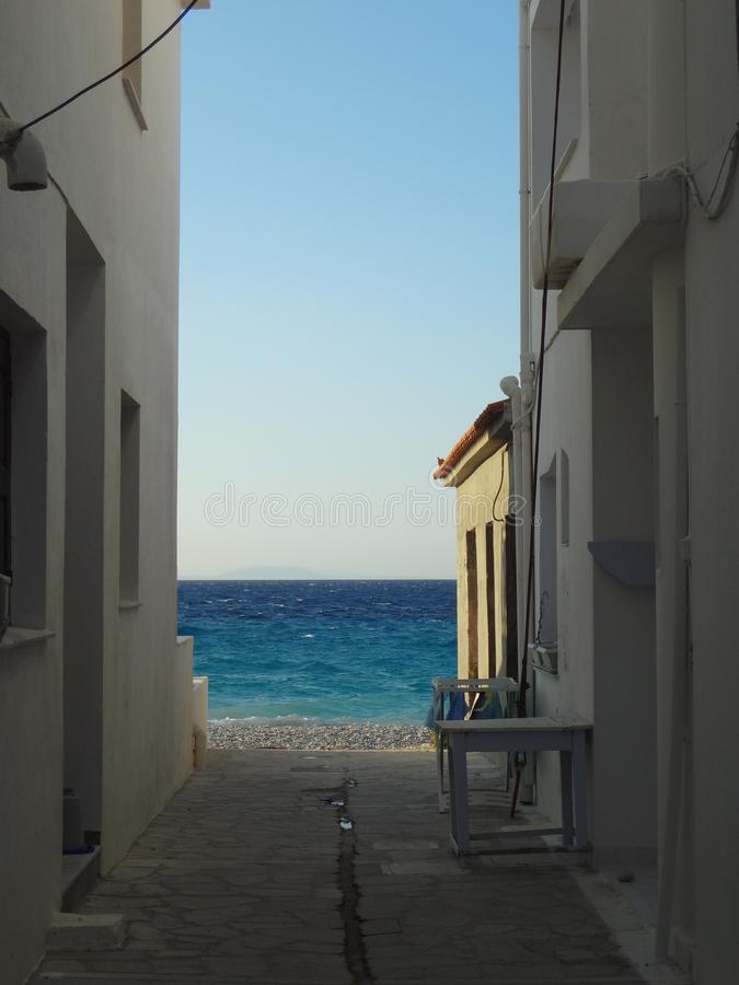 Sikt på det blåa havet till och med en smal gata arkivfoto