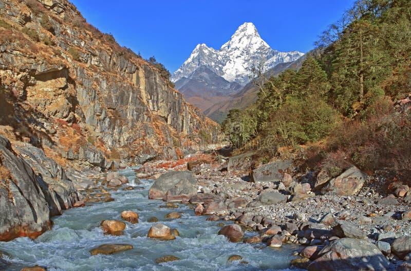 Sikt på det härliga Ama Dablam berget och den lilla floden, Everest region, royaltyfri bild
