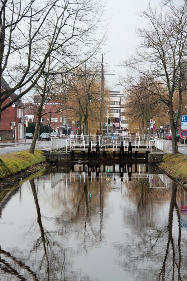 Sikt på en bro och dess reflexion på kanalen och omge i papenburg Tyskland arkivfoton