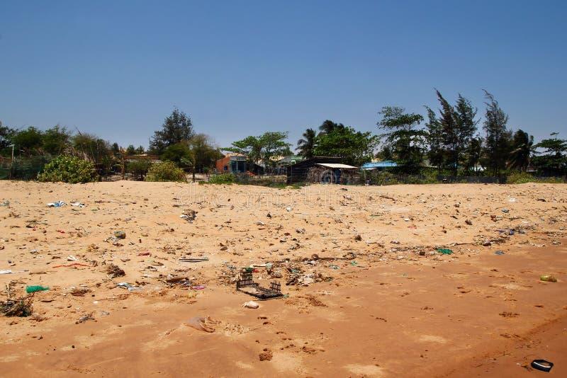 Sikt på en sandig strand nära till fiskeläget med mycket avskräde Förorening av en kustlinje muine vietnam royaltyfria foton
