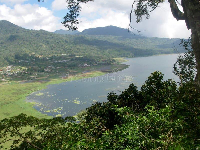 Sikt på en sjö och ett gräsplanberg i Bali arkivfoto