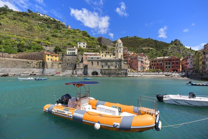 Sikt på fjärden av vatten med förtöjde fartyg och typiska färgrika hus i den lilla byn, Cinque Terre, Vernazza, Italien arkivfoto