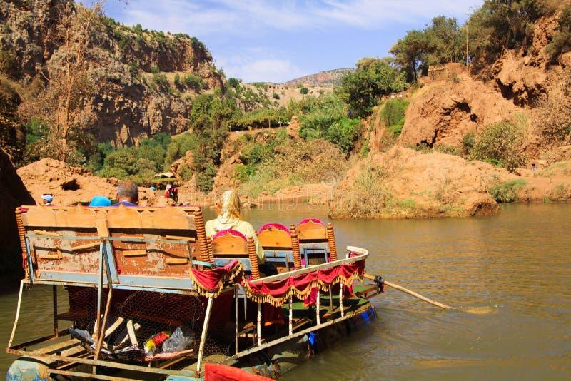 Sikt på floden i den Ourika dalen med den träfärgrika flotten och den muslim familjen - Marocko royaltyfri foto