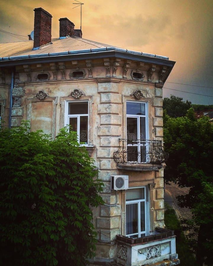 Sikt på gammalt hus med balkonger i sommardag Åskmoln över hus efter regn arkivfoton