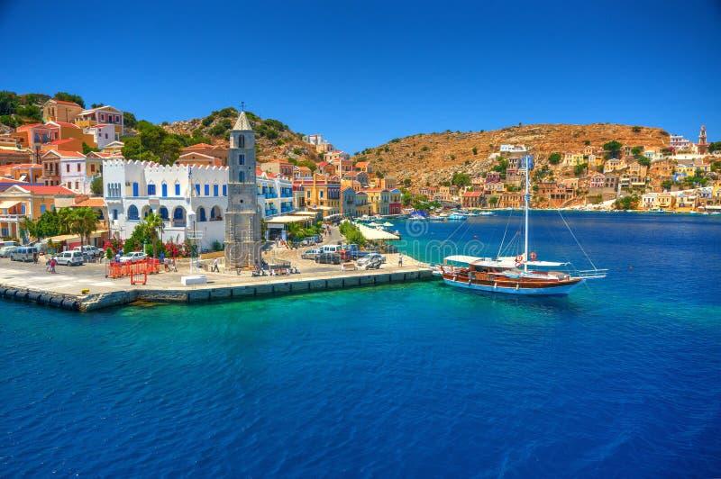Sikt på grekisk port för hamn för havsSimy ö, klassiska skeppyachter, hus på ökullar, fjärd för Aegean hav för turister Grekland  royaltyfri bild