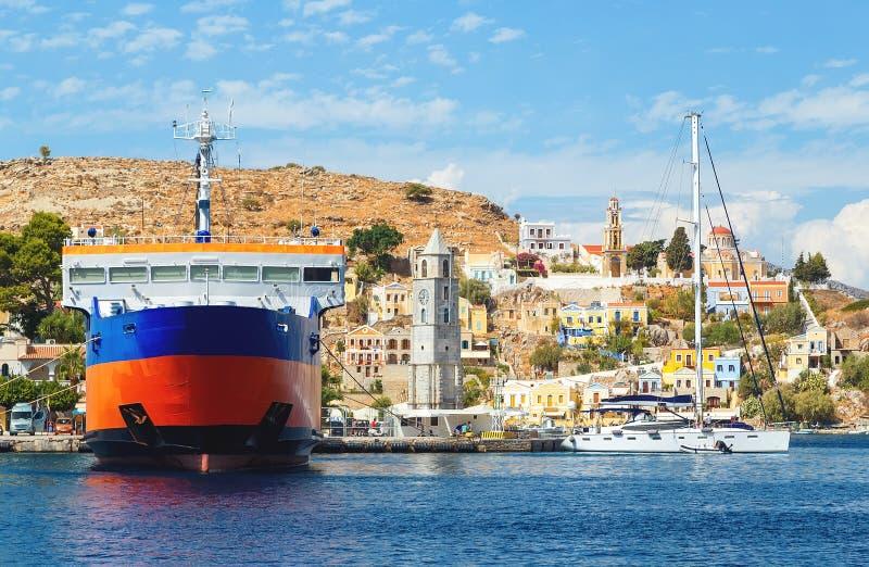 Sikt på grekisk port för hamn för havsSymi ö, klassiska skeppyachter, hus på ökullar, fjärd för Aegean hav för turister royaltyfri bild