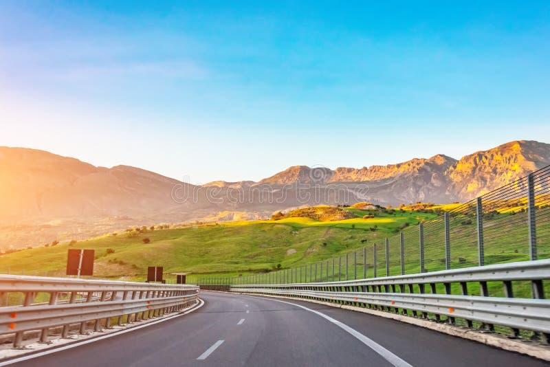 Sikt på huvudvägvägen och vänd i kullarna, berg i aftonen på soluppgång, lopptur royaltyfria bilder