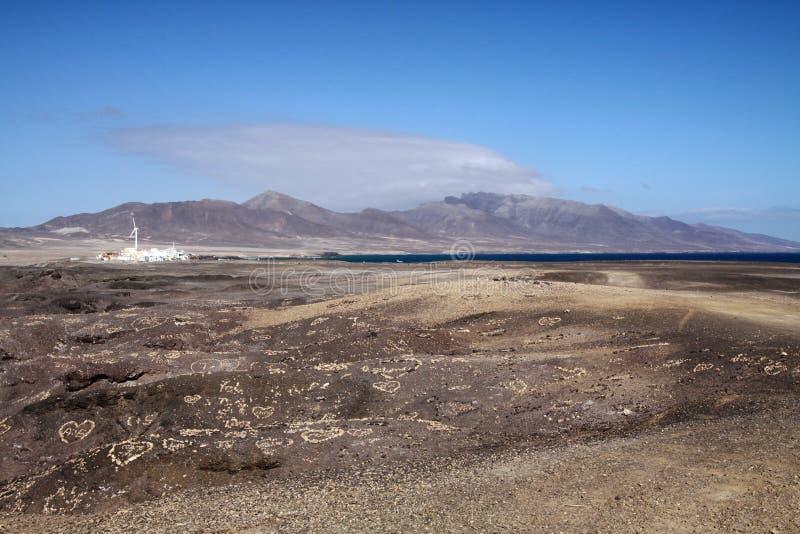 Sikt på liten vit by, bergskedja och fläck av det blåa havet över ändlöst kargt land, Fuerteventura, kanariefågelöar arkivfoto