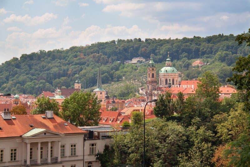Sikt på Prague tak med kyrkan och träd royaltyfria foton