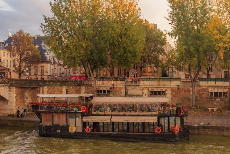 Sikt på Seinen och den sväva fartygrestaurangen La Nouvelle Seine nära den Notre Dame de Paris domkyrkan runt om solnedgång fotografering för bildbyråer