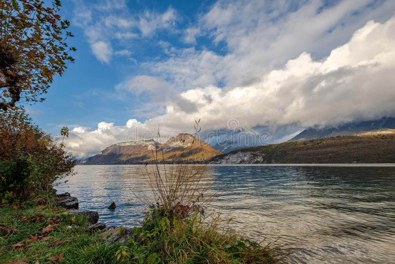 Sikt på sjön Annecy, Frankrike, med berg av härliga moln i bakgrunden arkivbilder