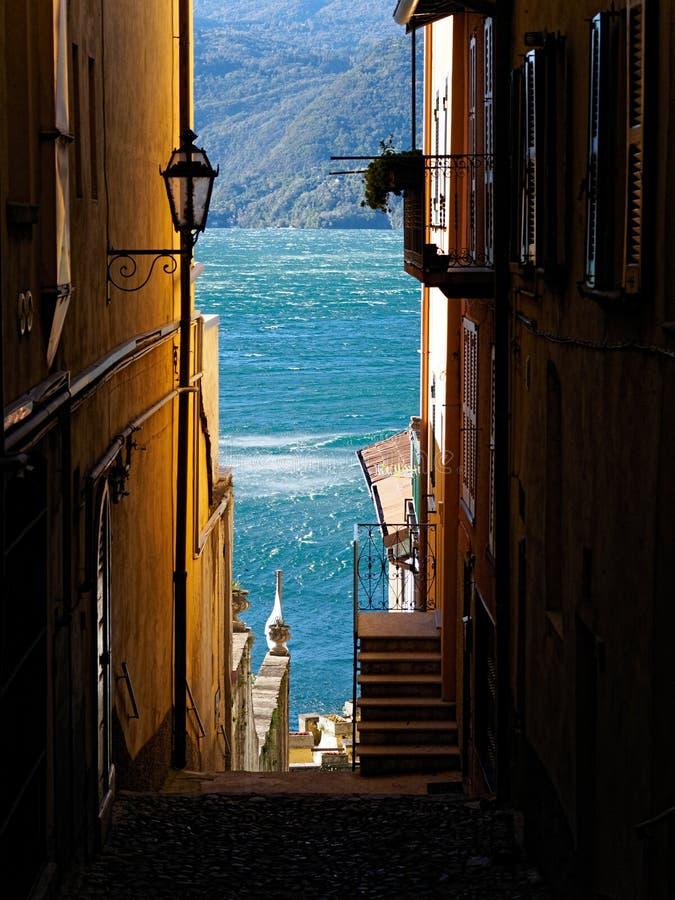 Sikt på sjön Como till och med en bystreet av Varenna fotografering för bildbyråer