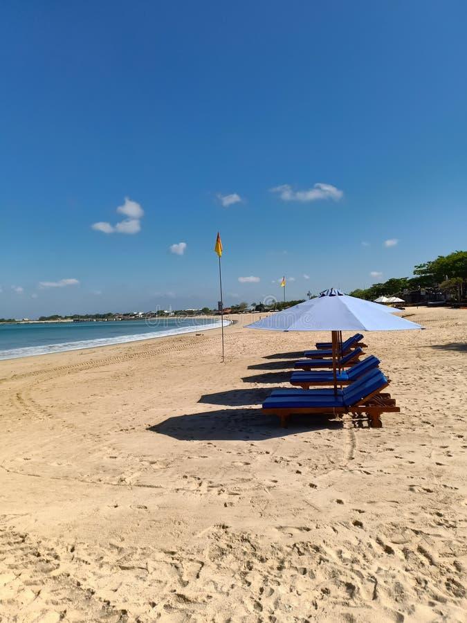 Sikt på solsäng och paraplyer på en Nusa Dua-strand arkivbilder