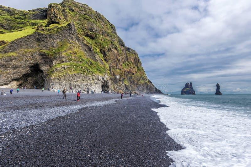 Sikt på stranden för Reynisfjara svartsand i sydliga Island Det Reynisfjall berget och Gardar basaltkolonner är på lämnat och arkivfoton