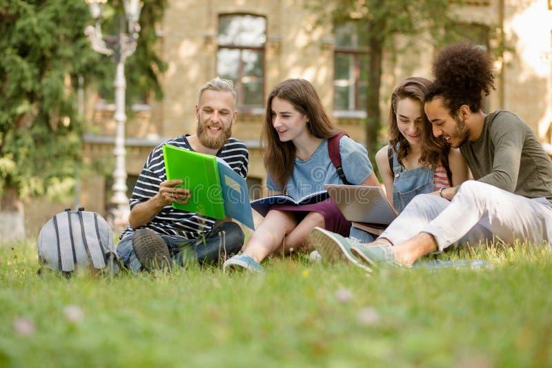 Sikt på studenter som sitter på gräsmatta som studerar i högskolaträdgård royaltyfri bild