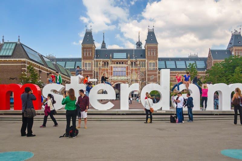 Sikt på tecknet för I Amsterdam med turister som är främsta av Rijksen royaltyfri fotografi
