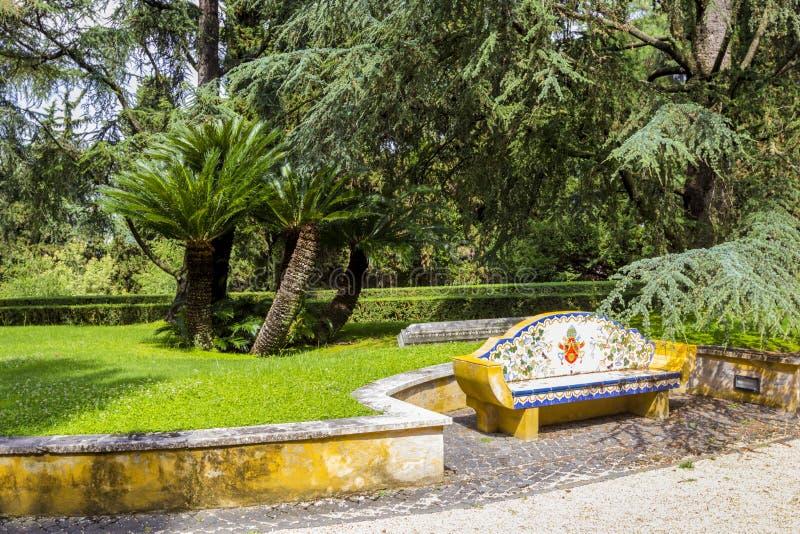 Sikt på Vaticanenträdgårdar med härliga gröna gräsmattor och träd och mosaikbänken, Rome, Italien royaltyfri foto