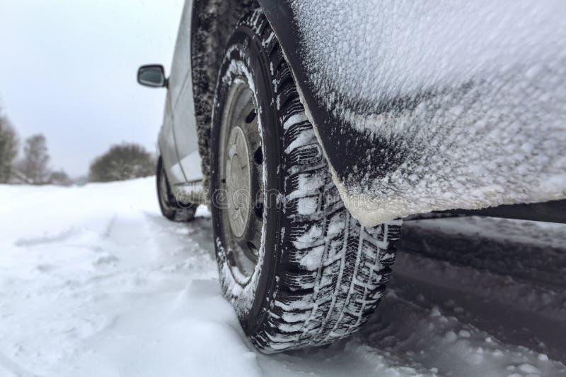 Sikt som fokuseras på bilgummihjulen och den tillbaka stötdämparen på vintervägen som täckas med snö Medel på den snöig vägen eft royaltyfri fotografi