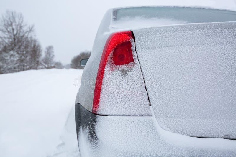Sikt som fokuseras p? de tillbaka r?da svansljusen av bilen och bilstammen eller bilk?ngan p? vinterv?gen som t?ckas med sn? Mede arkivbild
