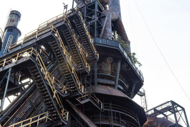 Sikt som ser upp till och med lager av trappa och gångbanor, övergett industriellt komplex royaltyfri foto