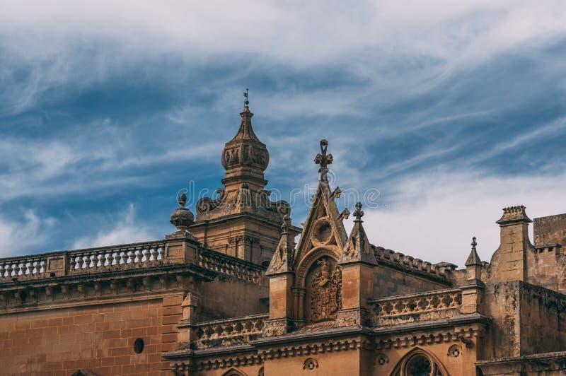 Sikt som ska ?vertr?ffas av casaen Courgion i Mdina och det Carmelite kyrkaKlocka tornet, Malta royaltyfri fotografi