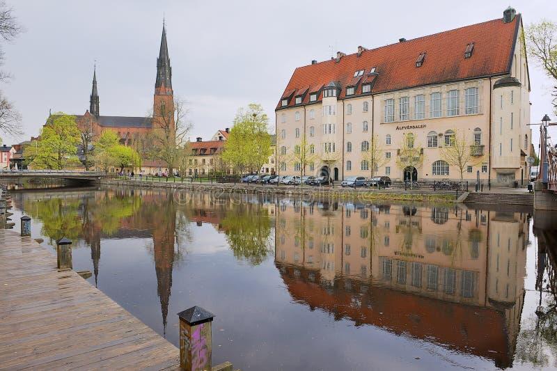 Sikt till de historiska byggnaderna som reflekterar i vattnet i Uppsala, Sverige royaltyfri fotografi
