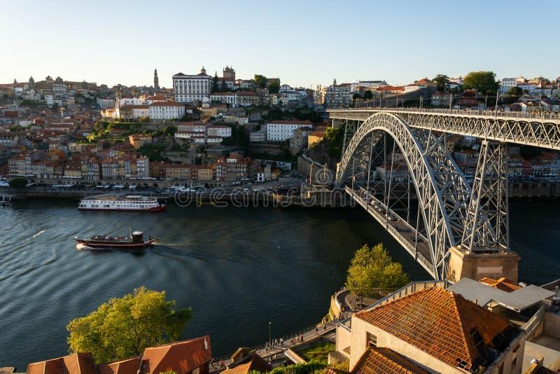 Sikt till den gamla staden av Porto med Det Luis bro och färgrika byggnader Varmt guld- ljus arkivfoton