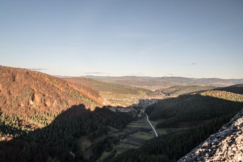 Sikt till den Jablonove byn med kullar som omkring täckas av den färgrika skogen från hikingtrail nära den Goticka branaen i höst fotografering för bildbyråer