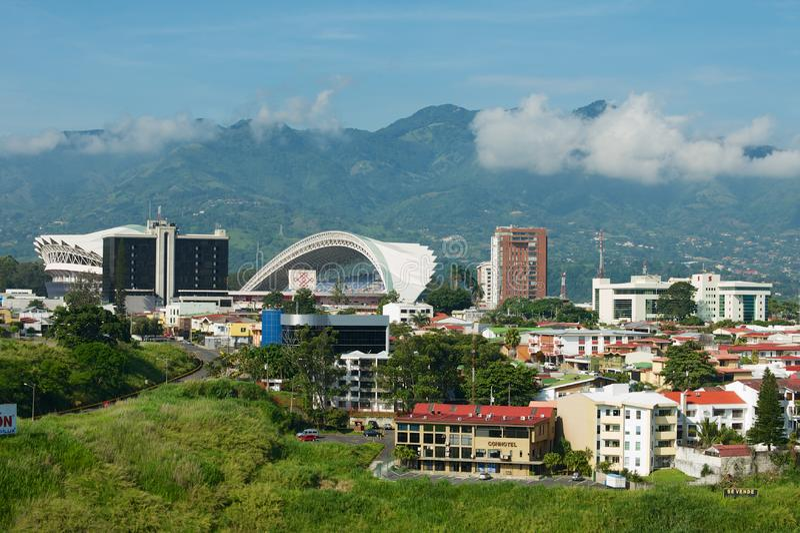 Sikt till den nationella stadion och de bostads- byggnaderna med berg på bakgrunden i San Jose, Costa Rica royaltyfri bild