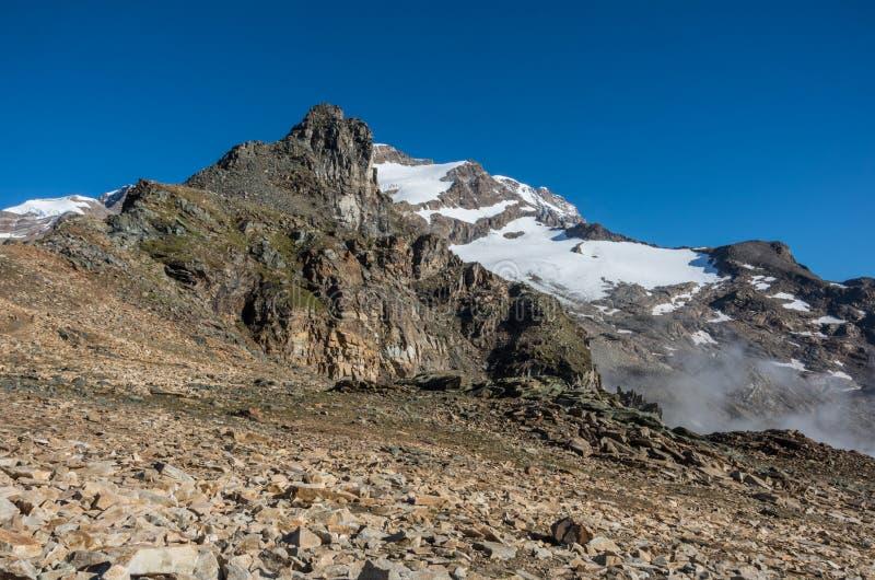 Sikt till den Stolemberg monteringen med den Vincent Pyramid monteringen och den Bors glaciären på bakgrund Monte Rosa massiv när fotografering för bildbyråer