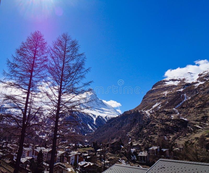 sikt till en liten by i de schweiziska fj?ll?ngarna royaltyfri bild