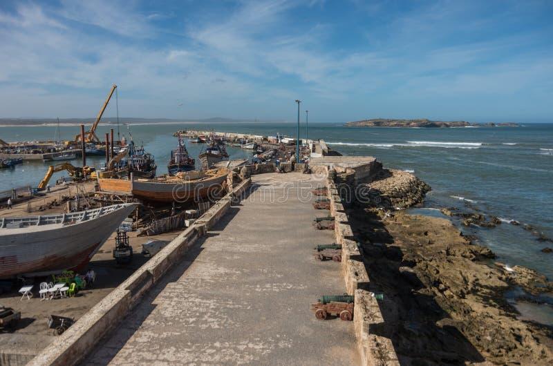 Sikt till fiskebåtar i den Essaouira hamnen och kanoner i Skala arkivbild
