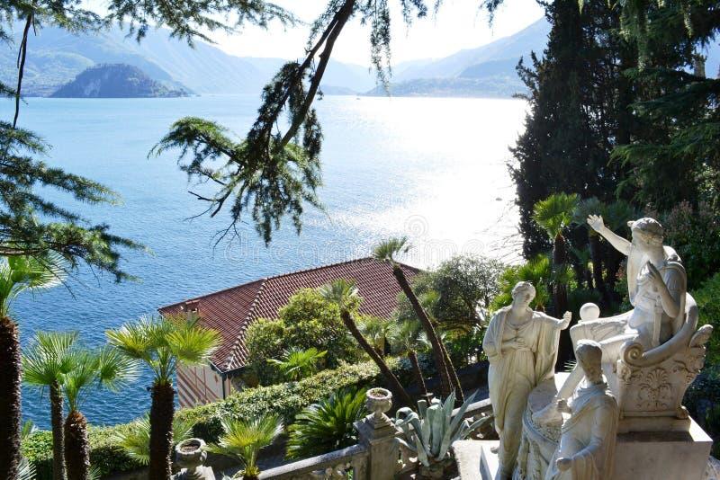 Sikt till forntida skulpturer av Giovan Battista Comolli av villan Monastero och panoramautsikt till sjön Como och Bellagio royaltyfria bilder