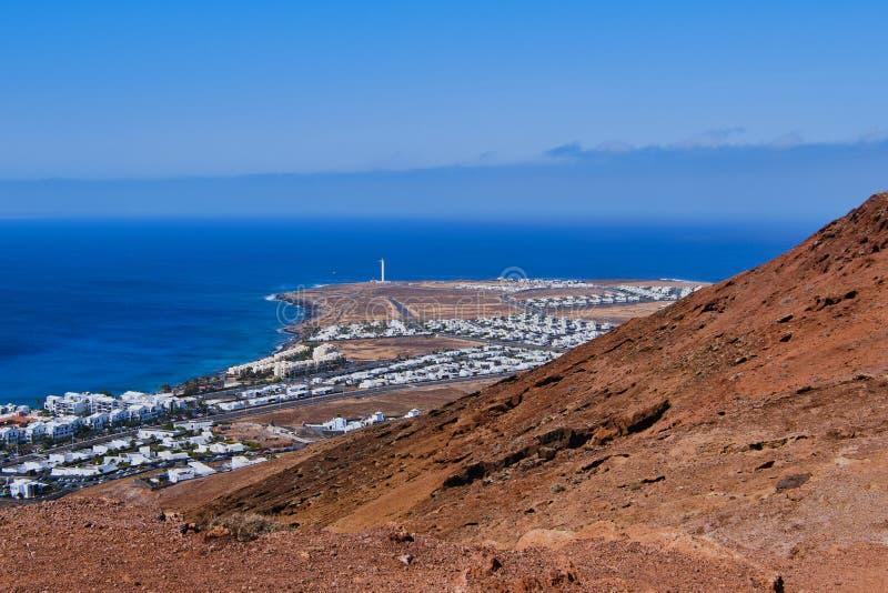 Sikt till fyren av Playa Blanca från den montana rojaen i Lanzarote royaltyfri bild