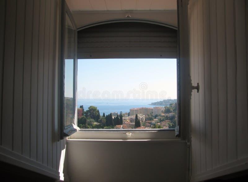 Sikt till medelhavet till och med det öppna fönstret, ` Azur, Frankrike för skjul D arkivbilder