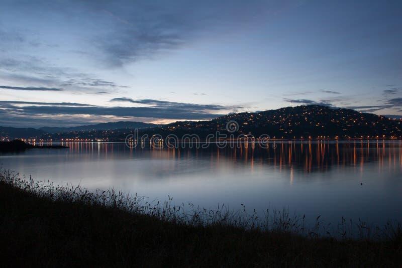 Sikt till nattstaden på kullen med ljus från kusten royaltyfria bilder